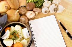 Plat de cocotte en terre avec les légumes et les herbes organiques sur le plan de travail de cuisine avec le livre de cuisine ou  Image libre de droits