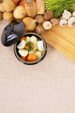 Plat de cocotte en terre avec les légumes et les herbes organiques sur le plan de travail de cuisine, l'espace de copie, vertical Photo stock