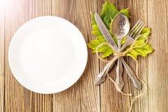 Plat de dîner de thanksgiving avec la fourchette, le couteau et les feuilles d'automne sur le fond en bois rustique de table Vue  images libres de droits