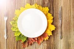 Plat de dîner de thanksgiving avec la fourchette, le couteau et les feuilles d'automne sur le fond en bois rustique de table Vue  photographie stock