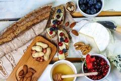 Plat de fromage - brie, camembert et canneberge, mûres, bruschette d'échantillon, fin de casse-croûte  carte Vue supérieure image libre de droits
