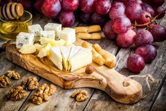 Plat de fromage : Camembert, parmesan, fromage bleu avec des batons de pain, écrous, miel et raisins Photo stock