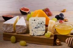 Plat de fromage Divers types de fromage avec des raisins, le miel, des figues et des écrous sur la table en bois rustique Image stock