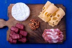 Plat de fromage et de viande avec des noix sur le fond en bois bleu Vue supérieure Photographie stock
