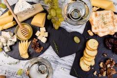 Plat de fromage L'assortiment du fromage avec des noix, panent un miel du plat en pierre d'ardoise Photos libres de droits