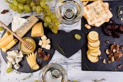 Plat de fromage L'assortiment du fromage avec des noix, panent un miel du plat en pierre d'ardoise Image stock