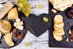 Plat de fromage L'assortiment du fromage avec des noix, panent un miel du plat en pierre d'ardoise Photo stock