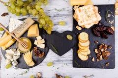 Plat de fromage L'assortiment du fromage avec des noix, panent un miel du plat en pierre d'ardoise Photographie stock libre de droits