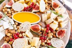 Plat de fromage Préparation délicieuse de fromage avec des croûtons de baguette, groseille rouge, figues douces, amande, miel sur photo libre de droits