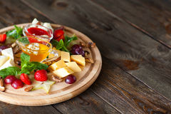 Plat de fruit et de fromage sur l'espace libre en bois Photo stock