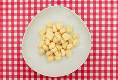 Plat de Gnocchi sur la table à carreaux rouge et blanche Photos stock