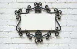 Plat de l'information dans le cadre forgé sur un mur de briques Images stock
