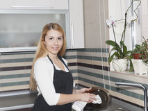 Plat de lavage de jeune femme dans la cuisine Photographie stock libre de droits