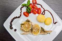 Plat de morue avec des citrons et des tomates Images stock