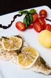 Plat de morue avec des citrons et des tomates Image stock