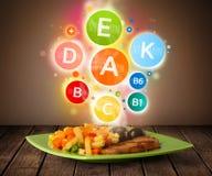 Plat de nourriture avec le repas délicieux et les symboles sains de vitamine Image libre de droits