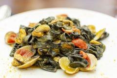 Plat de p?tes de fruits de mer, fettuccini noir italien avec des palourdes de vongole et moules photographie stock