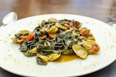 Plat de p?tes de fruits de mer, fettuccini noir italien avec des palourdes de vongole et moules image stock