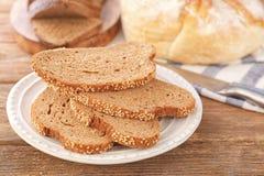 Plat de pain coupé en tranches sur la table en bois Photographie stock