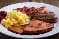 Plat de petit déjeuner - oeufs brouillés, lard, saucisse et jambon 2 Photographie stock