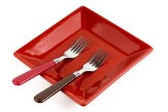 Plat de place rouge et deux fourchettes Images libres de droits