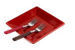 Plat de place rouge et deux fourchettes sur un blanc Photo stock