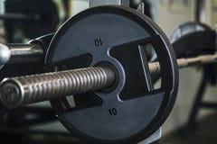 Plat de poids sur le barbell dans le gymnase, centre de fitness photographie stock libre de droits