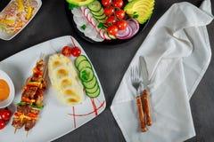 Plat de purée de pommes de terre, des tomates-cerises, du concombre et de la sauce crémeuse Brochettes grillées dans le restauran image libre de droits