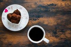 Plat de Saint Valentin et blanc de vintage, bonbons et coeur faits à partir du papier rouge, tasse de café noir Photo stock