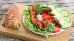Plat de salade, de mozzarella, de basilic, de chorizo, de concombre, de gerkins, de tomates et de laitue avec une baguette de cou Photo stock