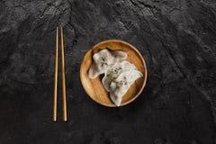 Plat des boulettes japonaises de gyoza sur la pierre noire d'ardoise photo stock