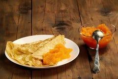 Plat des crêpes avec le caviar et une tasse avec le caviar sur la table Images stock