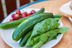 Plat des fraises, des épinards et des concombres frais Photo stock
