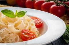 Plat des pâtes italiennes avec les tomates, le basilic et le fromage Image libre de droits