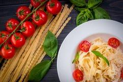 Plat des pâtes italiennes avec les tomates, le basilic et le fromage Photographie stock libre de droits