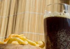 Plat des puces, un verre de bière foncée avec la mousse, bulles sur le fond en bois image libre de droits