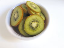 Plat des tranches de kiwi sur un fond blanc Photos stock