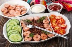 Plat divisé avec les saucisses frites, le riz rouge, les concombres, la tomate, la fourchette, le ketchup et la mayonnaise, servi images stock