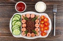 Plat divisé avec les saucisses frites, le riz rouge, les concombres, la tomate, le ketchup et la mayonnaise, fourchette sur la ta photos stock