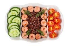 Plat divisé avec les saucisses frites, riz rouge, concombres, tomate d'isolement sur le blanc Vue supérieure photo stock