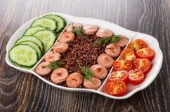 Plat divisé avec les saucisses frites, riz rouge, concombres, tomate, fourchette sur la table photographie stock