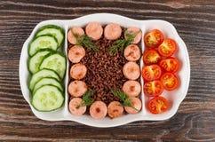 Plat divisé avec les saucisses frites, riz rouge, concombres, tomate sur la table foncée Vue supérieure images libres de droits