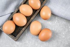 Plat en bois avec des oeufs de poulet Photographie stock