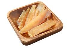Plat en bois avec le stockfisch de morceaux d'isolement sur le fond blanc Photo stock