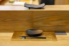 Plat en céramique noir vide sur la barre en bois, Japonais de style d'Omakase images libres de droits