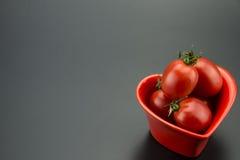 Plat en forme de coeur rouge et petites tomates Photographie stock libre de droits