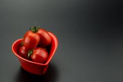 Plat en forme de coeur rouge et petites tomates Photos stock
