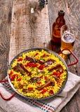 Plat et bière de Paella sur le Tableau en bois rustique Photographie stock libre de droits