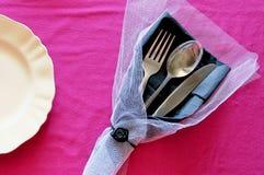 Plat et couverts sur un fond rose avec la décoration photographie stock libre de droits