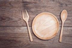 Plat et cuillère en bois sur la vue supérieure en bois de table Image libre de droits